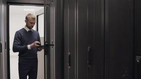 Ingeniero de las TIC que comprueba a los routeres en sitio del servidor usando un teléfono almacen de video