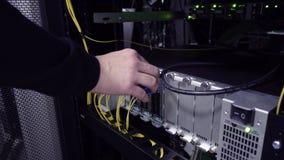 Ingeniero de las TIC que trabaja en un centro de datos con filas de los estantes del servidor y de los ordenadores estupendos ¡De almacen de video