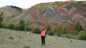 Ingeniero de minas, un geólogo en el chaleco reflexivo protector, guantes y casco, con el martillo a disposición metrajes