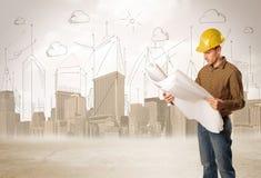 Ingeniero de negocio que acepilla en el emplazamiento de la obra con backgro de la ciudad Fotografía de archivo