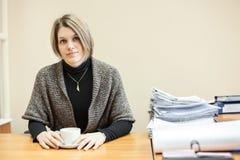 Ingeniero de sexo femenino con la taza de té en el escritorio del trabajo, copyspace Imagen de archivo libre de regalías