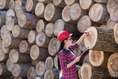 Ingeniero de sexo femenino del bosque al lado de registros Fotos de archivo libres de regalías