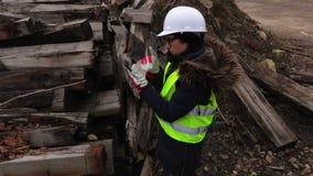 Ingeniero de sexo femenino que examina la basura en emplazamiento de la obra almacen de video