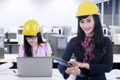Ingeniero de sexo femenino y su socio que trabajan en oficina Imagen de archivo