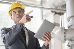 Ingeniero de sexo masculino joven con la tableta digital que señala lejos en industria Imagen de archivo libre de regalías