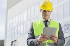 Ingeniero de sexo masculino joven en reflector-chaleco y el casco de protección usando industria exterior de la tableta digital Fotos de archivo