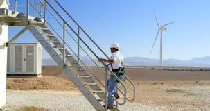 Ingeniero de sexo masculino que camina arriba en el parque eólico 4k almacen de video
