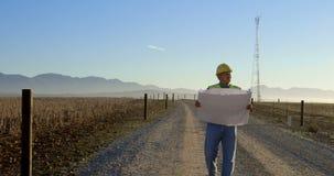 Ingeniero de sexo masculino que camina con el modelo en el parque eólico 4k almacen de video