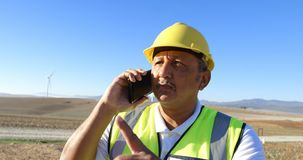Ingeniero de sexo masculino que habla en el teléfono móvil en el parque eólico 4k almacen de video