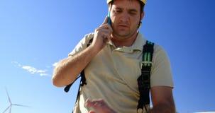 Ingeniero de sexo masculino que habla en el teléfono móvil en el parque eólico 4k almacen de metraje de vídeo