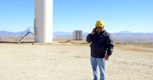 Ingeniero de sexo masculino que habla en el teléfono móvil en el parque eólico 4k metrajes