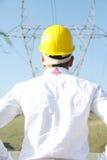 Ingeniero de sexo masculino que se coloca en la estación de la electricidad Imagenes de archivo