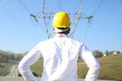 Ingeniero de sexo masculino que se coloca en la estación de la electricidad Foto de archivo libre de regalías