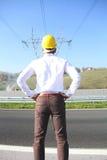 Ingeniero de sexo masculino que se coloca en la estación de la electricidad Fotos de archivo libres de regalías