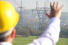 Ingeniero de sexo masculino que se coloca en la estación de la electricidad Fotografía de archivo libre de regalías