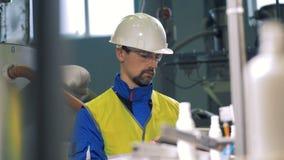 Ingeniero de sexo masculino que trabaja con una tableta, comprobando las máquinas de la planta almacen de video
