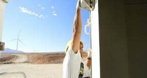 Ingeniero de sexo masculino que trabaja en el parque eólico 4k almacen de video