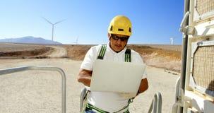 Ingeniero de sexo masculino que usa el ordenador portátil en el parque eólico 4k almacen de video