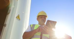 Ingeniero de sexo masculino que usa la tableta digital cerca en el parque eólico 4k metrajes