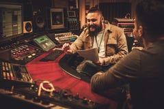 Ingeniero de sonido y músicos que trabajan en el estudio de grabación del boutique Foto de archivo