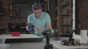 Ingeniero del amo del arte de la habilidad del retrato centrado en la perforaci?n de un agujero con la herramienta en el fondo de almacen de metraje de vídeo