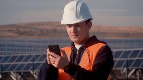 Ingeniero del aspecto caucásico en un casco blanco y un chaleco anaranjado con miradas serias en su teléfono móvil y a almacen de video