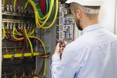 Ingeniero del electricista en el trabajo que examina la conexión de cableado de la línea eléctrica del poder de alto voltaje fotografía de archivo