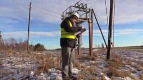 Ingeniero del electricista que comprueba la documentación cerca del transformador almacen de video