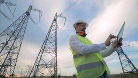Ingeniero del electricista que trabaja con la tableta cerca de línea eléctrica almacen de video