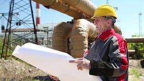 Ingeniero del mantenimiento con el dibujo del proyecto en la estación del electropower del calor almacen de video