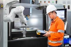 Ingeniero del mantenimiento que programa la mano robótica automática con el CNC imagen de archivo