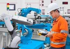 Ingeniero del mantenimiento que programa robótico automatizada en la industria 4 fotos de archivo