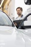 Ingeniero del mantenimiento que sostiene la tableta mientras que examina el coche en el taller de reparaciones Foto de archivo