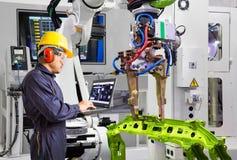Ingeniero del mantenimiento usando el objeto automotriz del apretón del robot del control de ordenador portátil en la fábrica ele foto de archivo libre de regalías