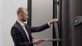 Ingeniero del servidor que trabaja en sitio del centro de datos usando el ordenador portátil almacen de metraje de vídeo