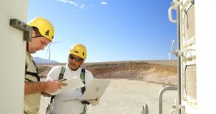 Ingeniero dos que discute sobre el ordenador portátil en el parque eólico 4k metrajes