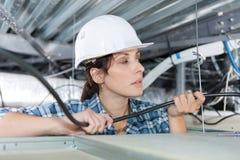 Ingeniero eléctrico de sexo femenino que trabaja con los alambres fotos de archivo