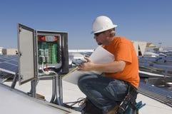 Ingeniero eléctrico Holding Book While que analiza la caja de la electricidad Fotos de archivo libres de regalías