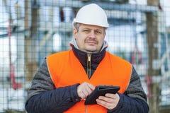 Ingeniero eléctrico con la tableta cerca de la subestación eléctrica Fotos de archivo