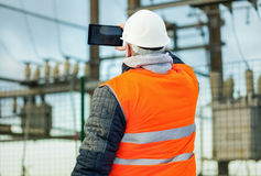 Ingeniero eléctrico con la tableta en la subestación eléctrica Foto de archivo