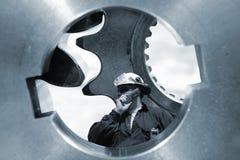 Ingeniero en el casco de protección dentro de los árboles del engranaje Imágenes de archivo libres de regalías