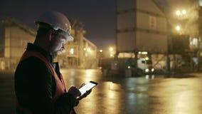 Ingeniero en el casco de protección que comprueba el cargamento del camión con una tableta en fábrica de la industria pesada almacen de metraje de vídeo