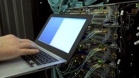 Ingeniero en el cuarto del servidor con un ordenador portátil en el fondo de un servidor óptico con las luces que destellan Ecobu almacen de video