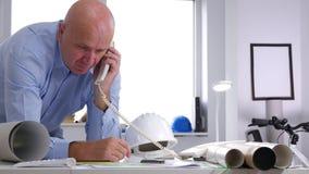 Ingeniero en oficina de la arquitectura que habla para llamar por teléfono a problemas técnicos metrajes