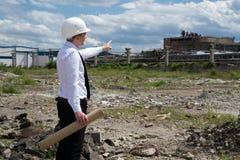 Ingeniero en sitio que señala el edificio viejo Foto de archivo