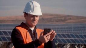 Ingeniero en un chaleco anaranjado vía el teléfono, divulgado a sus superiores sobre la situación de los paneles solares en la em almacen de metraje de vídeo