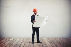 Ingeniero en un desgaste formal que mira modelos Imágenes de archivo libres de regalías
