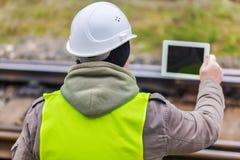 Ingeniero ferroviario con la tableta en los carriles Imagen de archivo libre de regalías