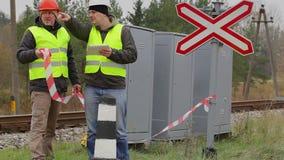 Ingeniero ferroviario con la tableta y el trabajador con la cinta amonestadora metrajes