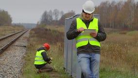 Ingeniero ferroviario con la tableta y el trabajador en fondo almacen de metraje de vídeo